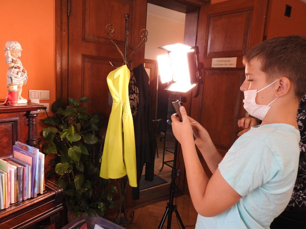 Osoba robiąca zdjęcie teleonem komórkowym, na którą skierowane jest światło z lampy.
