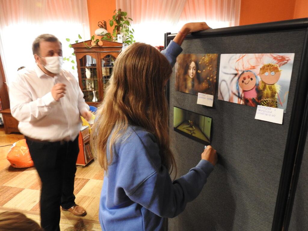 osoba dorosła przygląda się, jak młodsza postać przyczpia na tablicy koolrową kartkę.