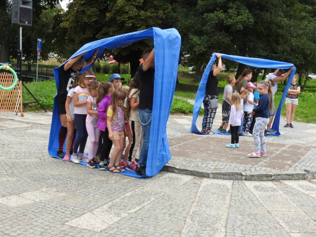 Dwie dorosłe osoby, po środku nich grupka dzieci. Wszyscy stoja usatwieni jeden za drugim, otoczeni niebieską szarfą.