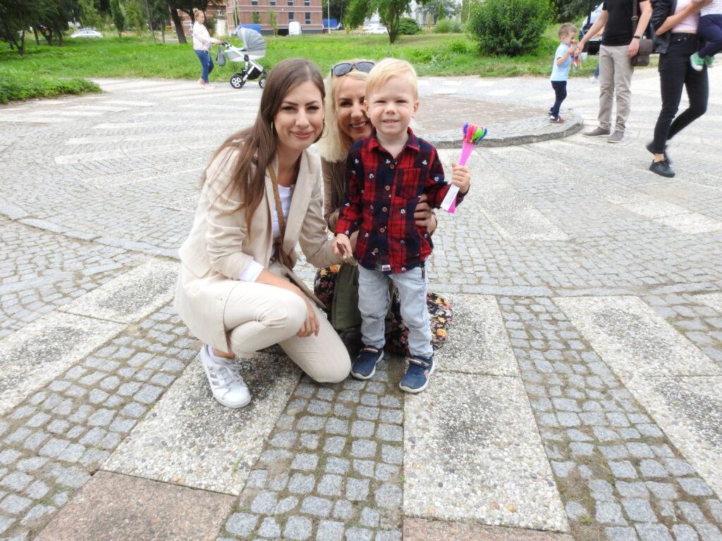 Chłopiec oraz dwie dorosłe kobiety pozuja do zdjęcia. dziecko trzyma w ręku jakiś przedmiot.