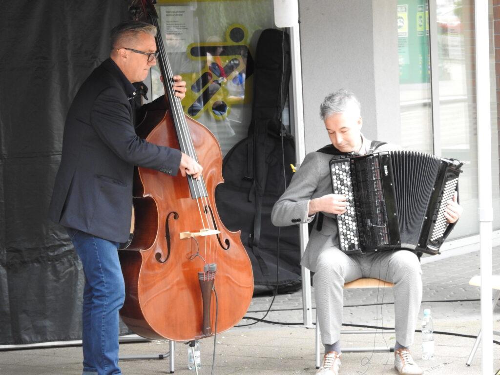 Dwóch mężczyzn grających na instrumentach.