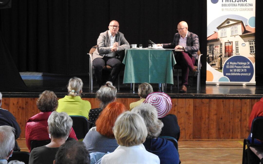 Dwóch mężczyzn przy stoliku, wewnątrz pomieszczenia. Jeden trzyma mikrofon. Przed nimi na krzesłach siedzą ludzie.