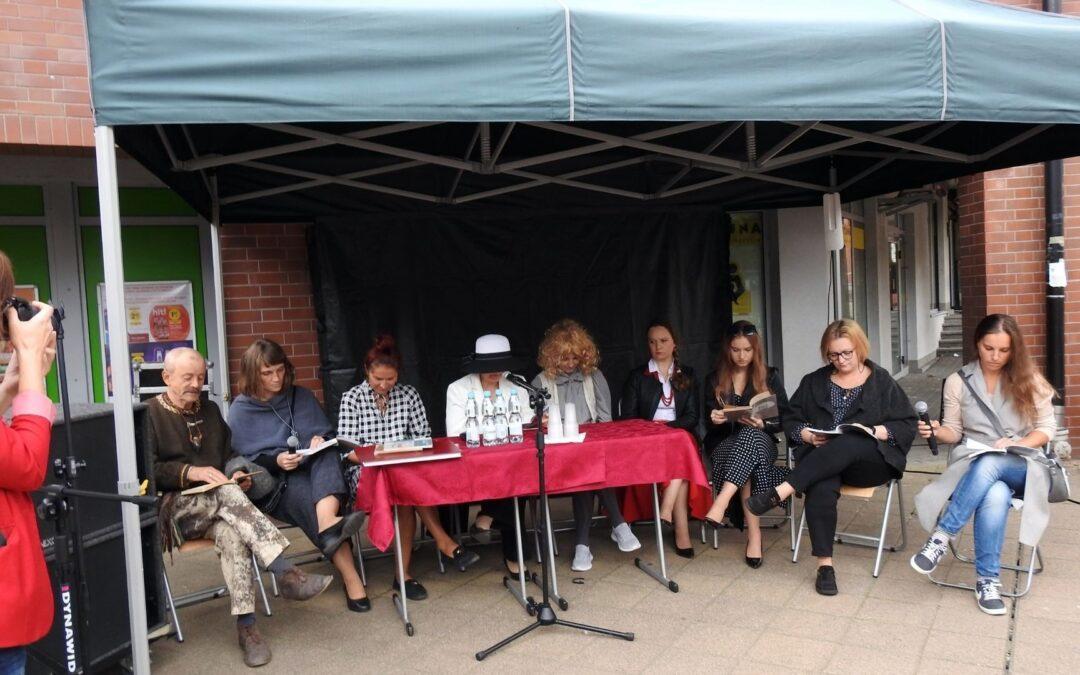 Zdjęcie przedstawiające 10 osób siedzących na świeżym powietrzu. Przed nimi stoi mikrofon.