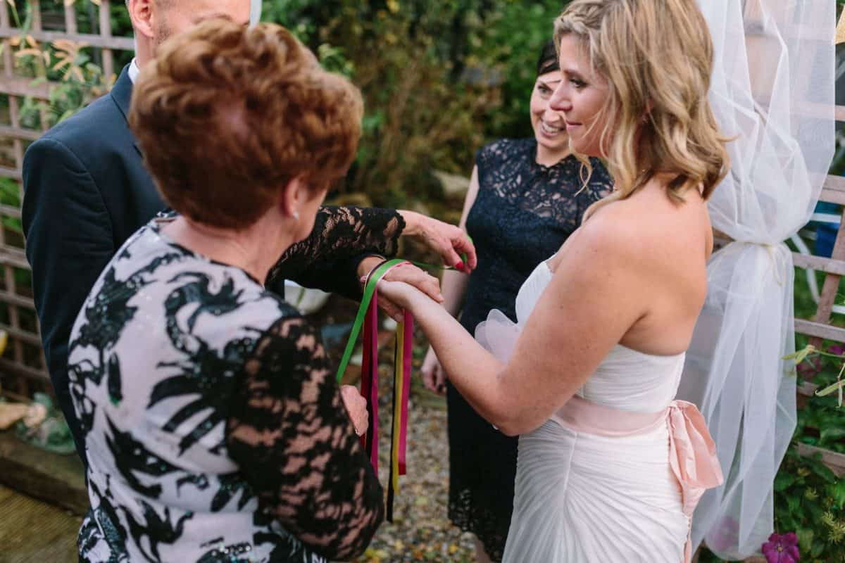 Mother lays the hand fasting ribbons during sons wedding ceremony