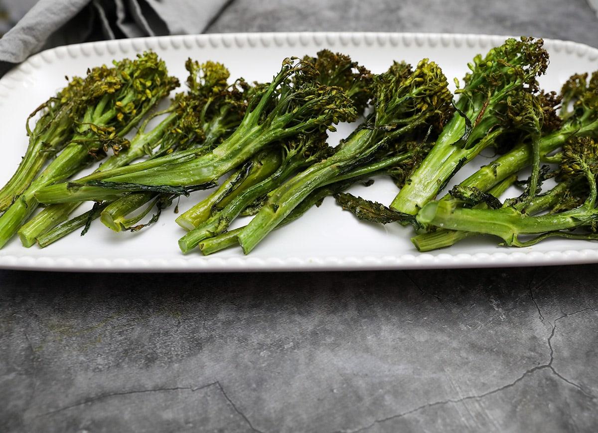 roasted broccolini on white platter on grey background