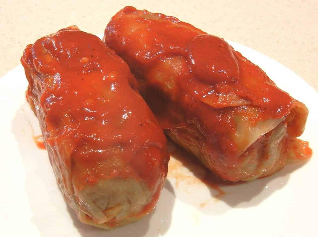 Polish golabki stuffed cabbage rolls with sauce on top.