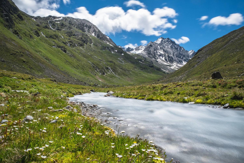 Fluss fließt durch Wiesen mit Berghängen