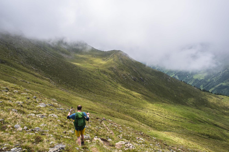 Wanderer mit Stöcken läuft durch Graslandschaft