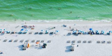 White sand, green surf and beach chairs in a line on the beach at gulf shores