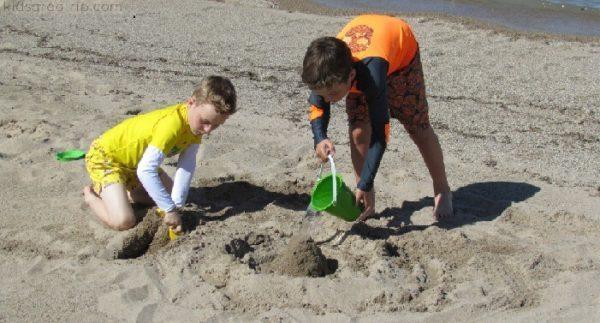Kids play on a lake michigan beach.