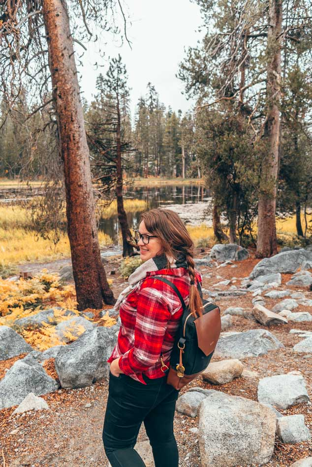 Exploring Yosemite National Park in the fall in a red flannel shirt, scarf, and backpack.