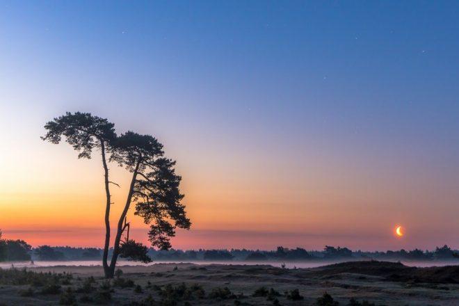 Fotograaf Andre Van Der Meulen Zonopkomst Maanondergang Aekingerzand met ondergaande zon