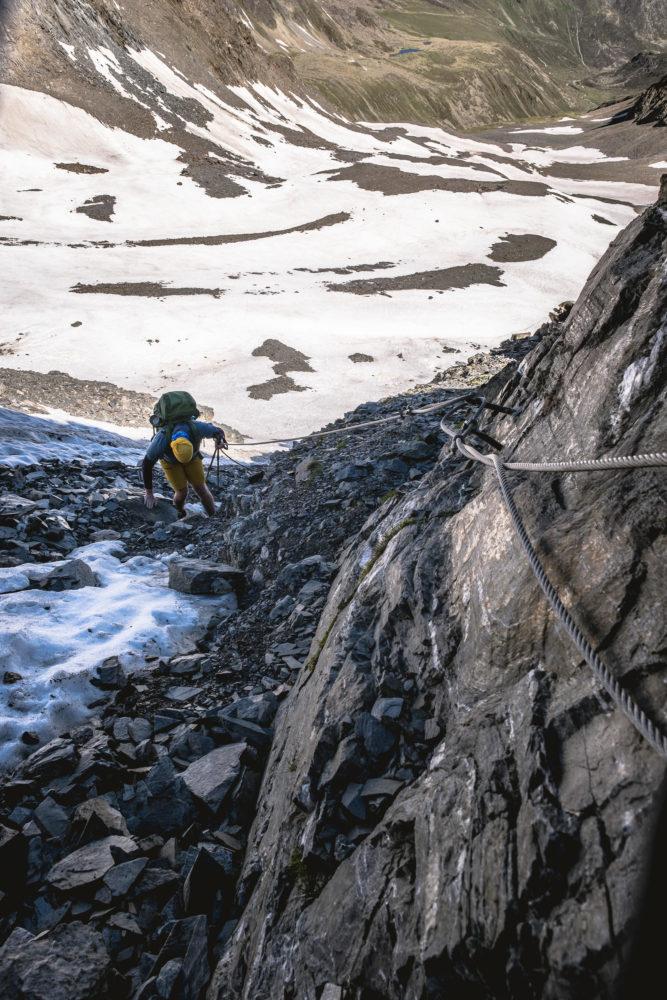 Wanderer steigt am Stahlseil eine Schuttrinne hinab
