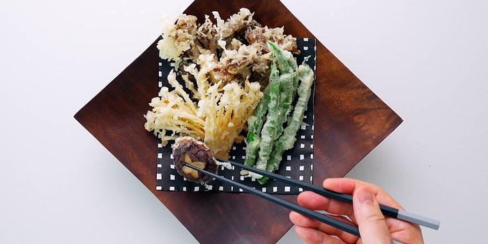 Plating vegan tempura mushrooms.