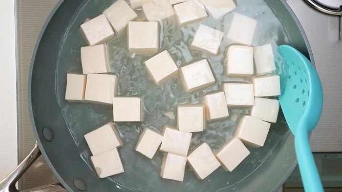 Simmering tofu in salt water to remove excess liquid.
