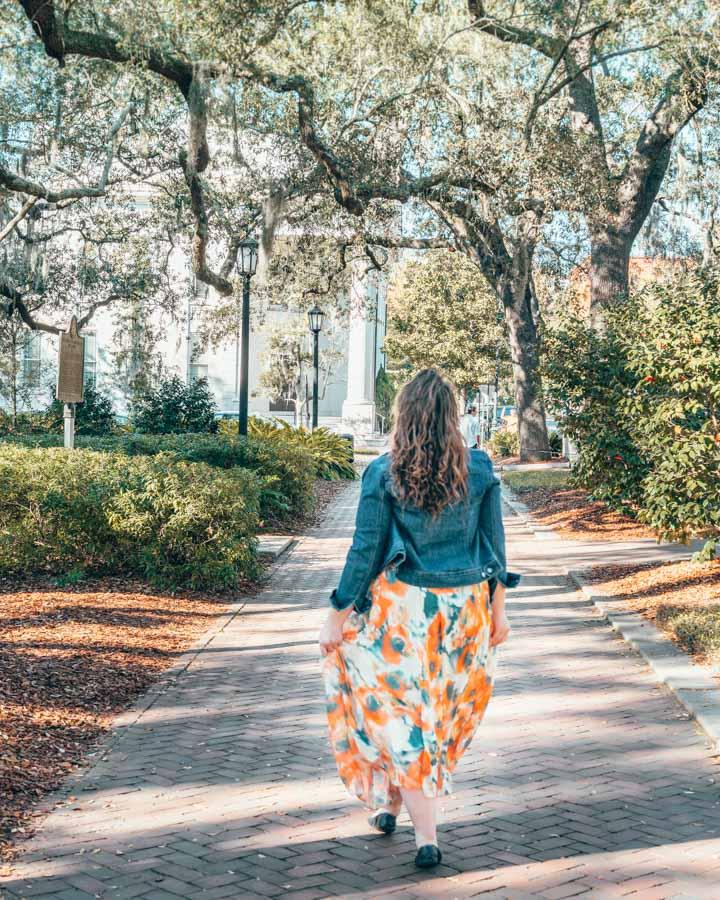 Girl in a denim jacket and orange skirt walking in a shadowy square Savannah Georgia
