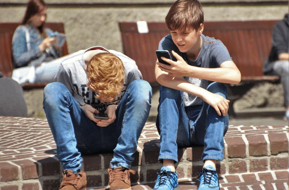 teenage boys on smart phones taking selfies screen time