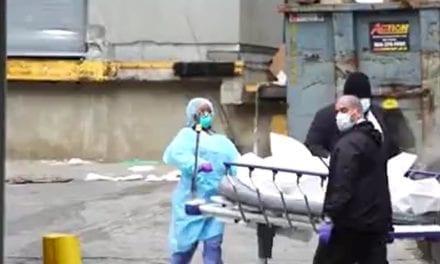 Corpos de mortos sendo transferidos para caminhões refrigerados