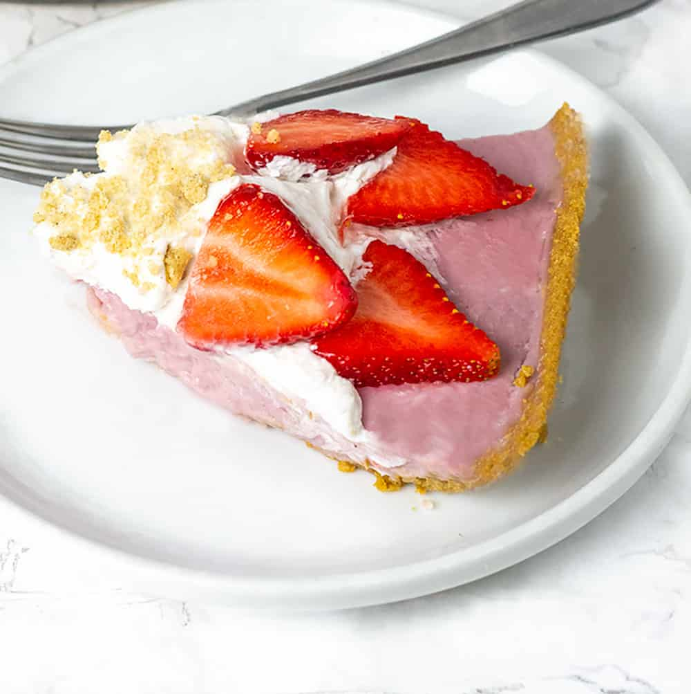 Best vegan strawberry cream pie, pink strawberry pie topped with white vegan coconut whipped cream, sliced strawberries and garnished with sprinkle of crushed golden graham crackers