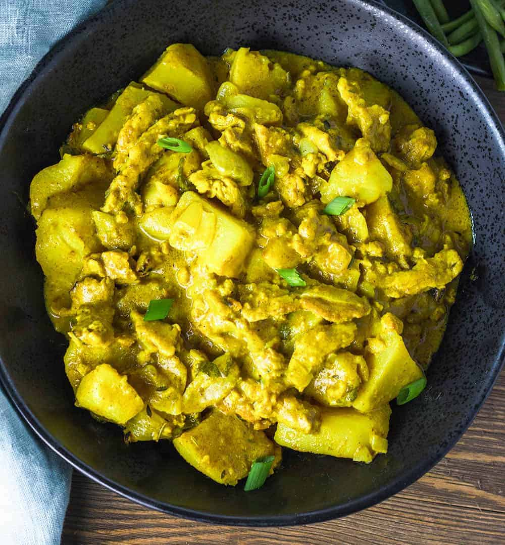 vegan curry chicken and potatoes in a black bowl on a wooden background