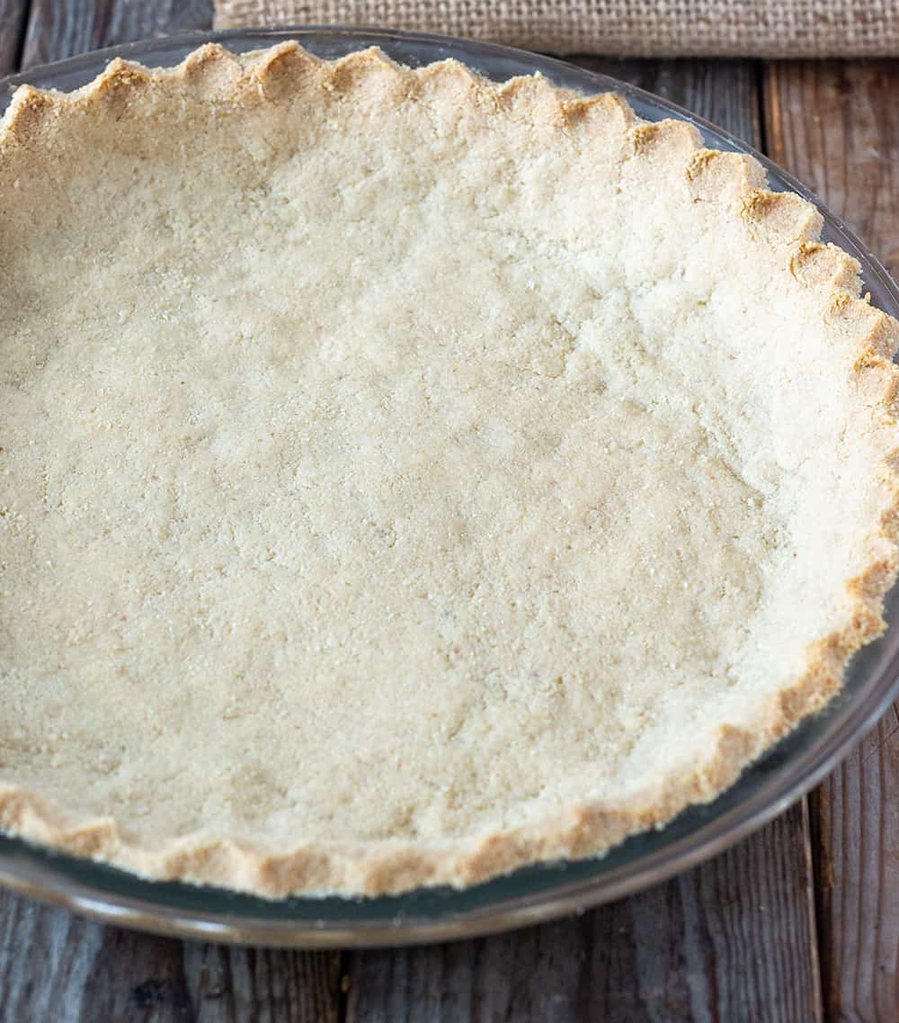 Finished baked almond pie crust in glass pie plate, made with almond flour, vegan butter, maple syrup. salt. and vanilla