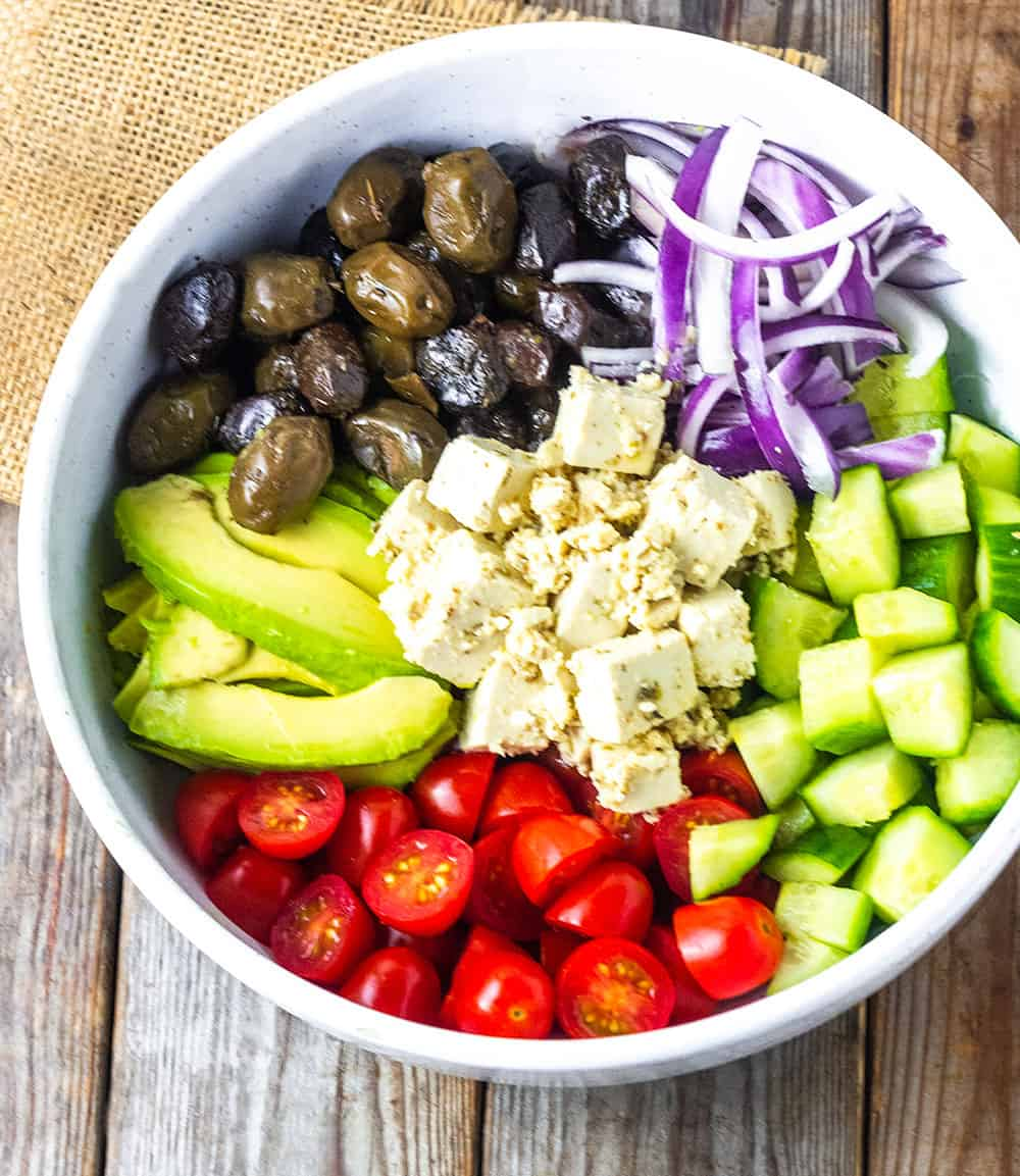 vegan feta cheese in the center of greek salad with chopped tomatoes, cucumber, red onion, olive and avocado in a white bowl on a brown wooden board