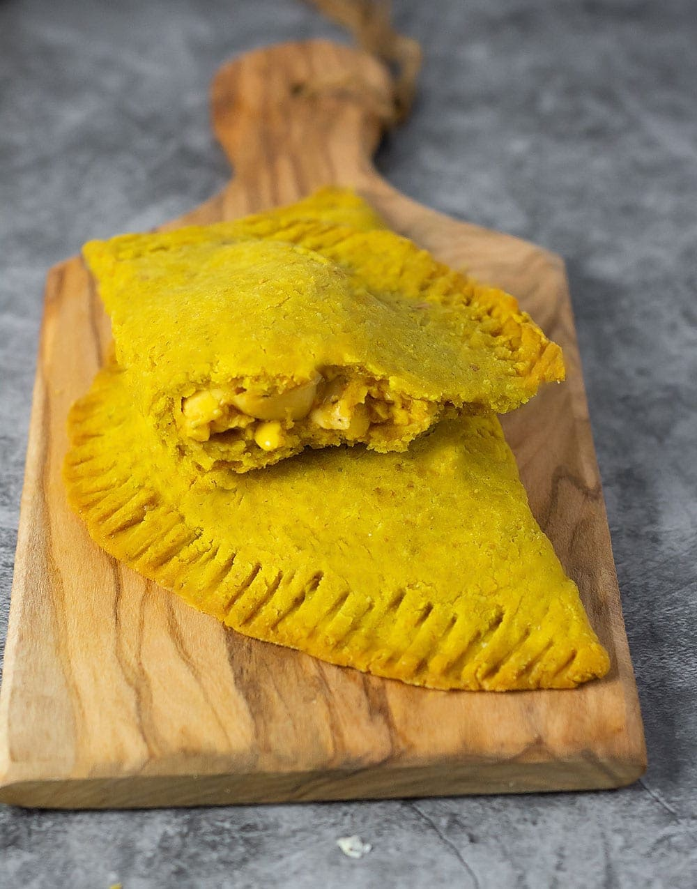 Jamaican ackee patty, two patties on a cutting board with grey background