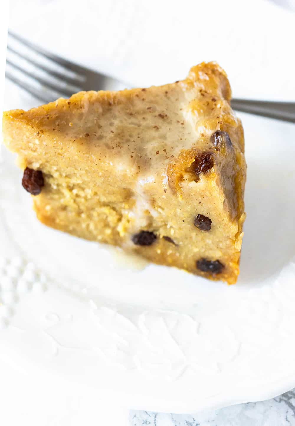 slice of cornmeal pudding on white plate with fork