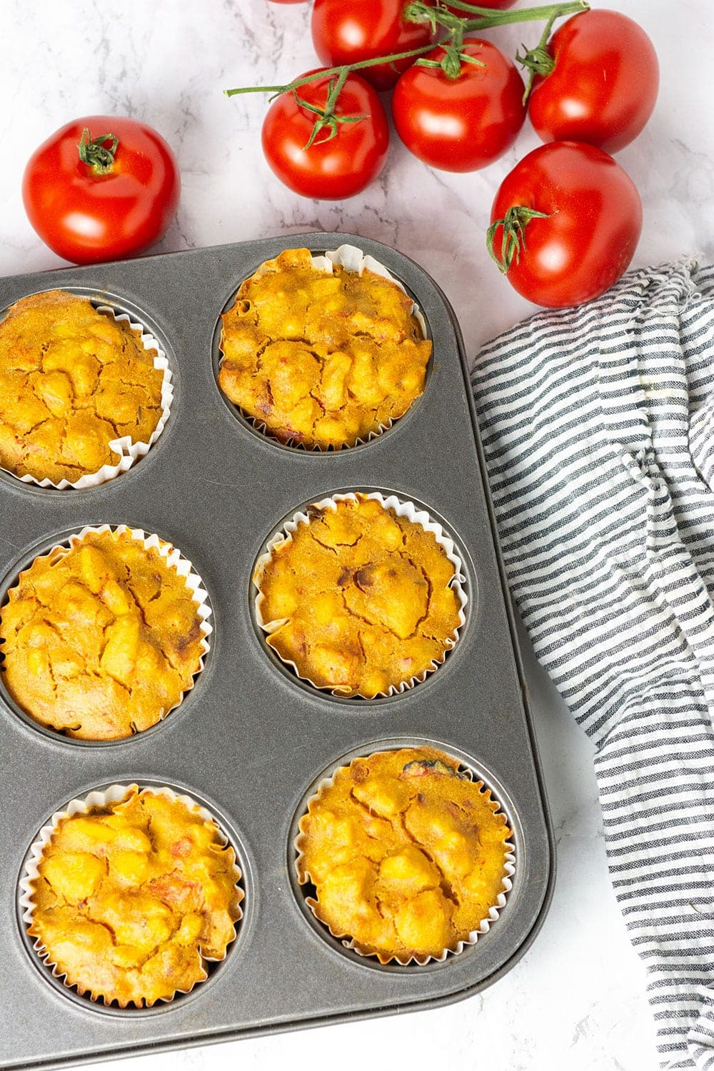 Easy vegan quiche in muffin pan with tomatoes in the background and a black and white stripe napkin to the side on a marbled background