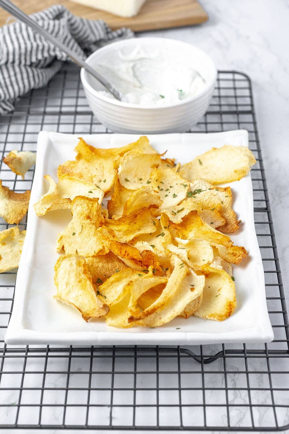 jicama chips on a white rectangular platter with a black and white napkin and a white bowl with yogurt dip