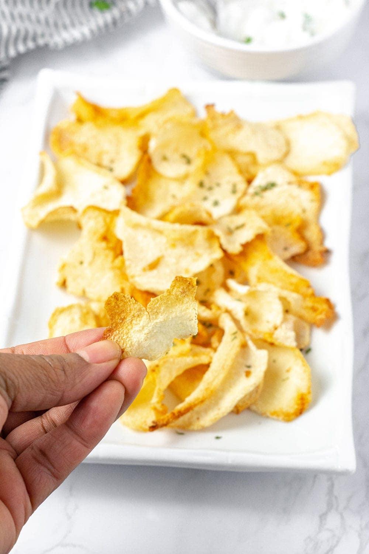 holding crispy jicama chips over a platter of chips on a white plate