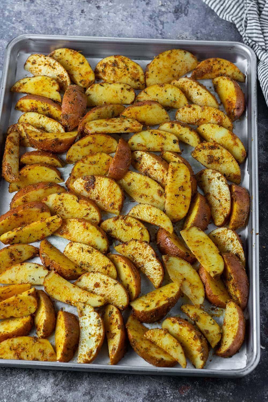 Seasoned cajun fries on sheet pan before being baked