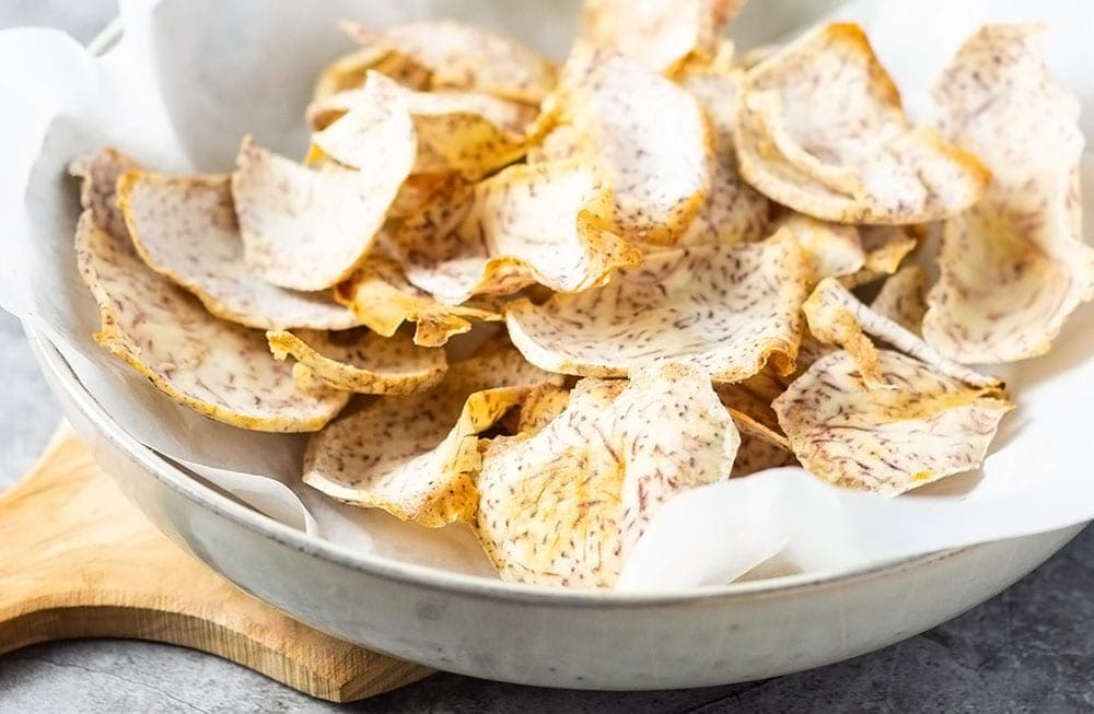 taro chips in a bowl on a cutting board