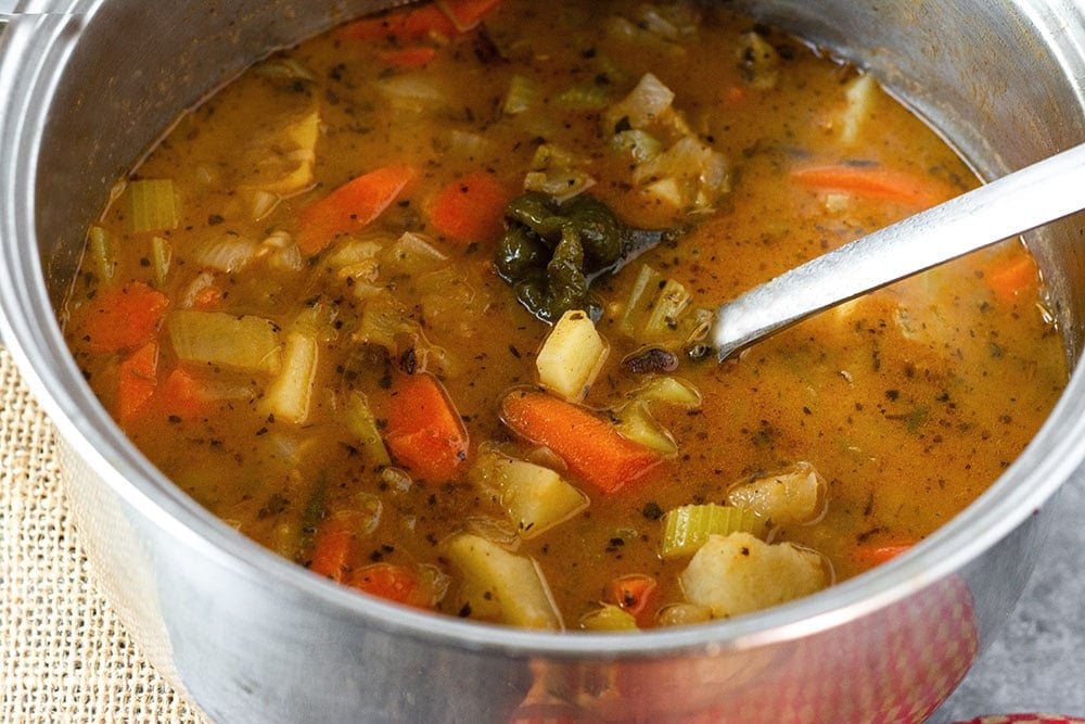 Stainless steel pot of Jamaican pigeon peas stew (gungo peas) a large spoon