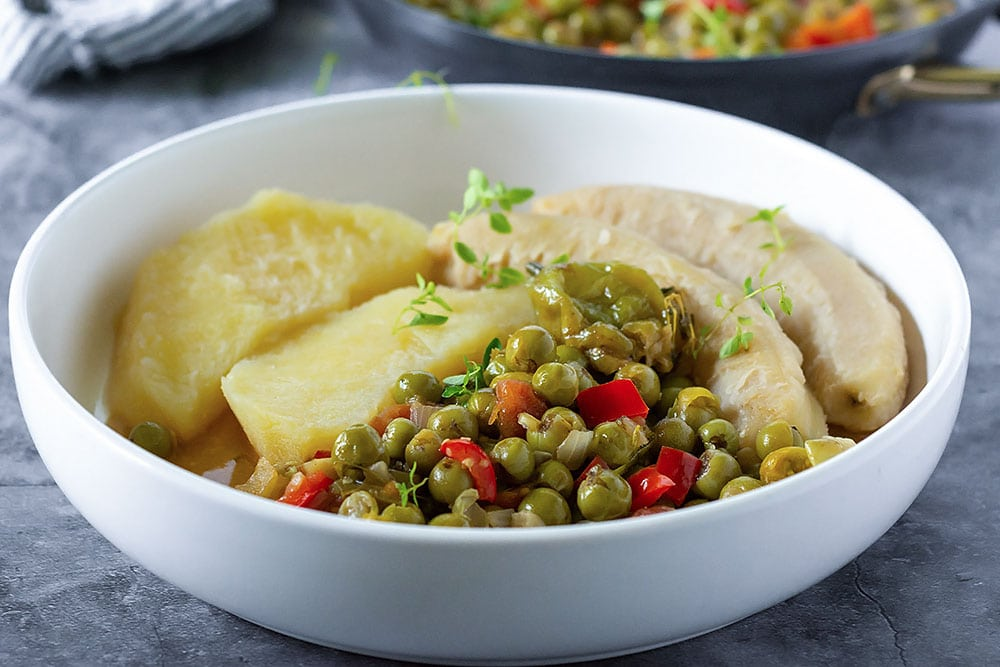 Susumba stew recipe in a bowl, yellow yam, green banana in a white bowl on a stone background