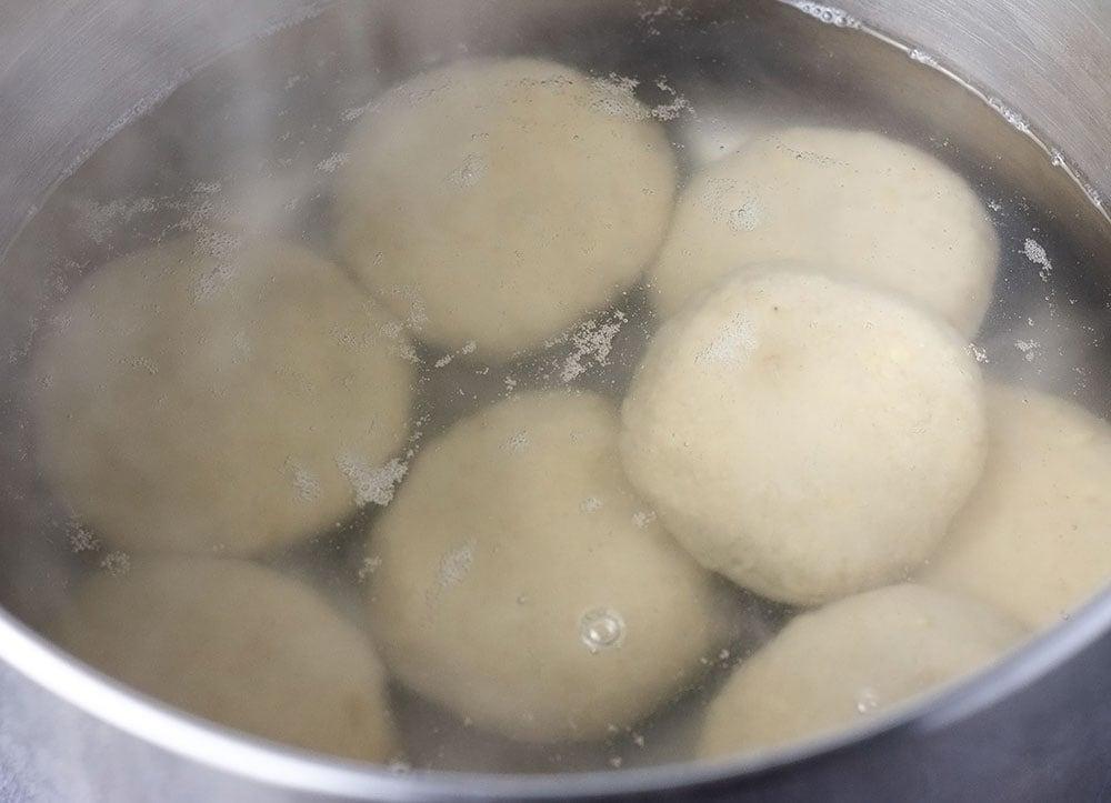 Green banana dumpling recipe, dumplings being boiled in water in a pot