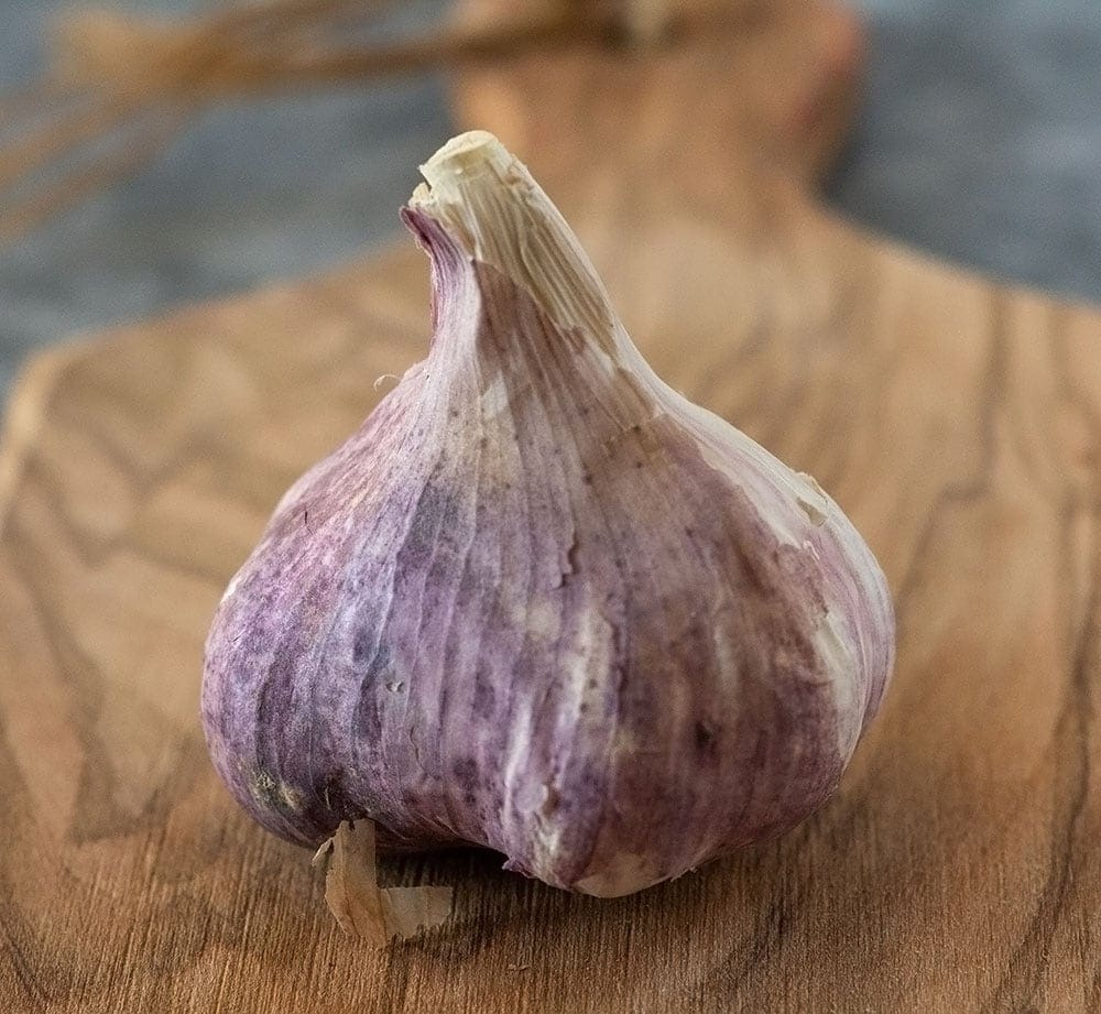 Garlic bulb on a cutting board for roasting