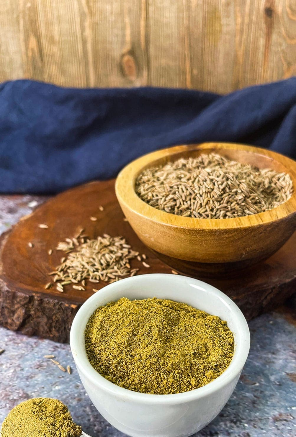 dried cumin in a wooden bowl with coriander powder in a white bowl
