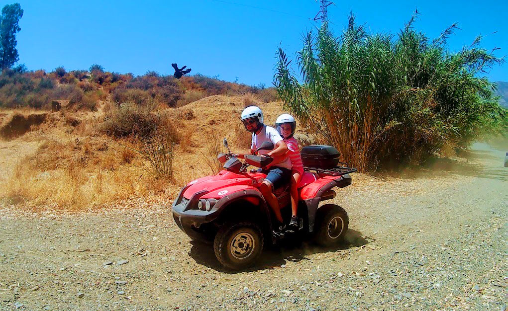A father and a kid on a quad riding laughing