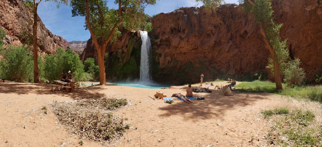 Sandy beach with people laying in the sun - Havasu FAlls in the background
