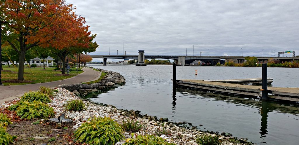 Paved trail meanders between orange maple trees and the riverbank. A dock and bridge frame the watery image of Fox River Trail, one of best Things to do in Green Bay Wisconsin
