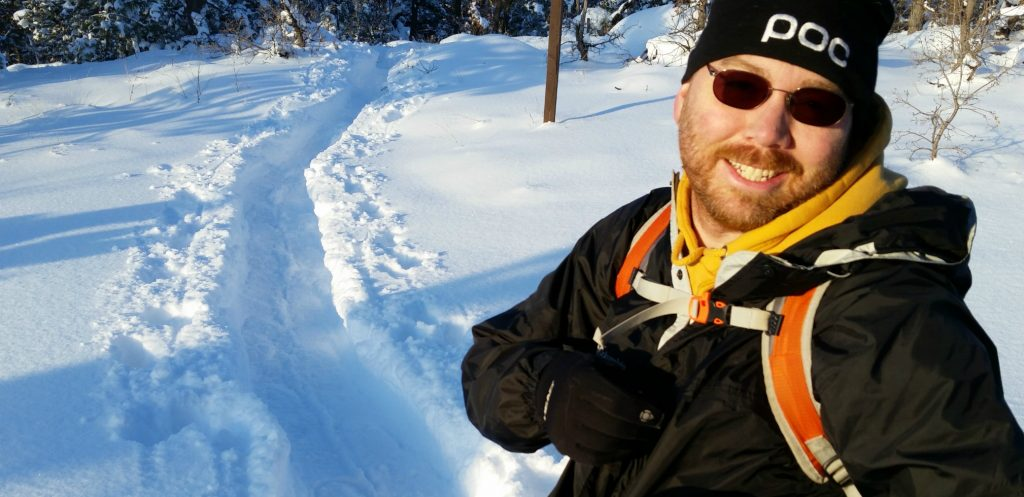 man stands on snowshoe trail with backpack filled with Backcountry Essentials for Hiking & Skiing, the Ten Essentials of Hiking