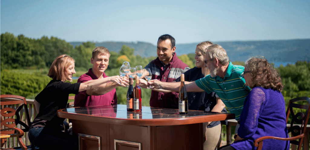 Family of dad, mom and kids and grandma toast wine glasses at one of the best wineries in Finger Lakes