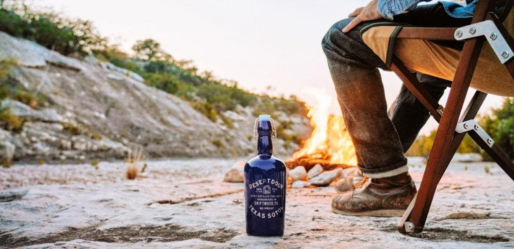 blue bottle of sotol sits on desert floor with a campfire and an sitting in camp chair behind the bottle of Texas sotol
