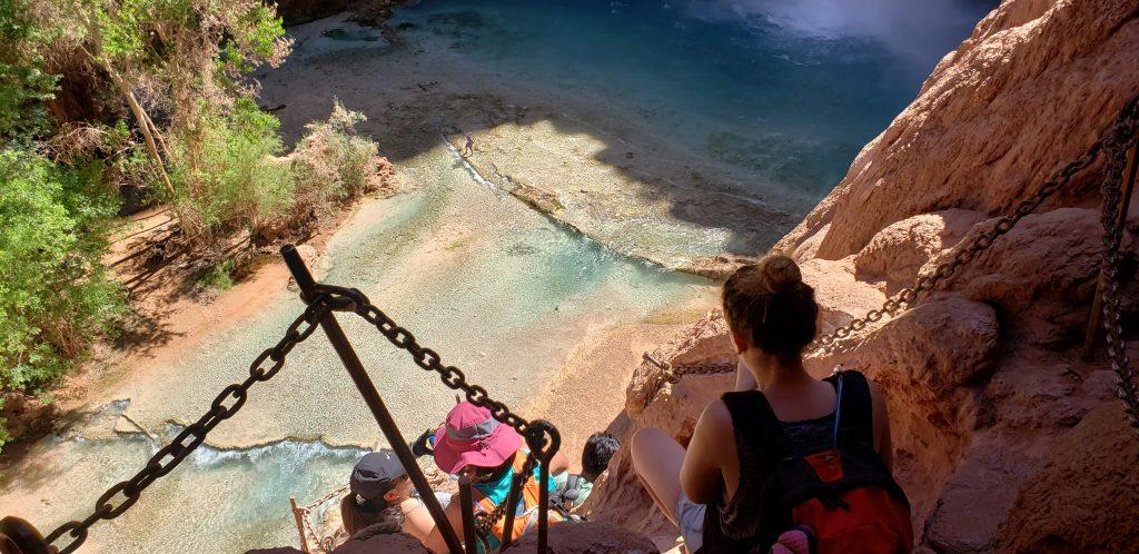 Hikers climbing down steep ladder at Mooney Falls
