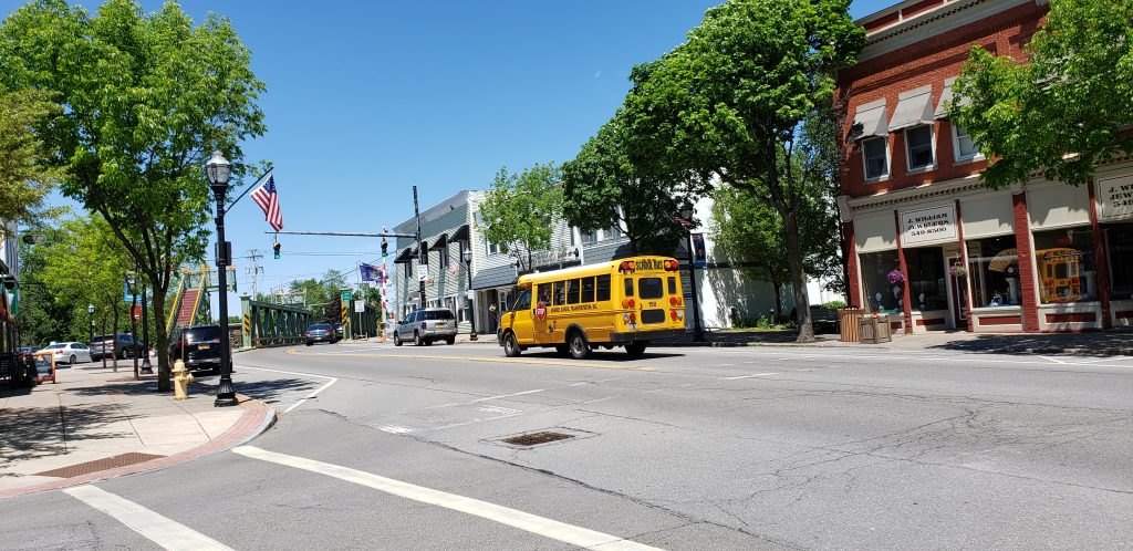 Erie Canal town street scene with American flags, school bus and lift bridge - Spencerport