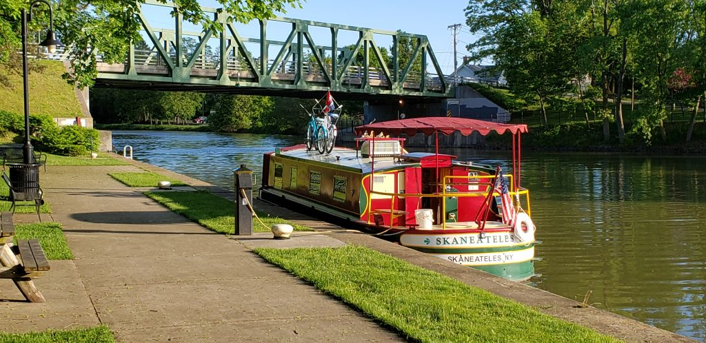 Packet boat in water tied at Pittsford Terminal with historic bridge in background on canal boat holidays United States