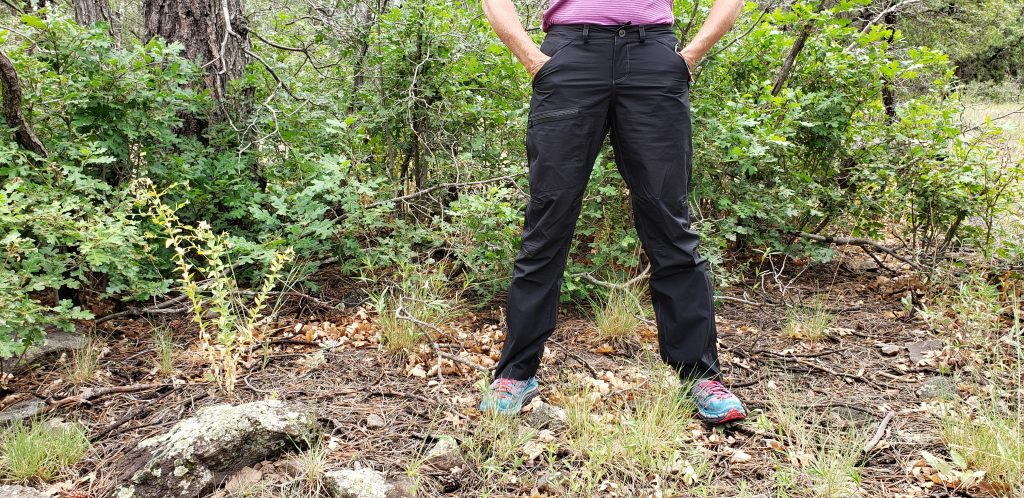 Unstoppable Stacey stands in black KÜHL rain pants with both hands in front pockets