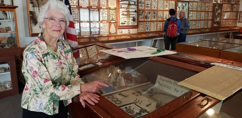Silver-haired woman points to display case of authentic Wild West artifacts. Behind her displays line the walls.