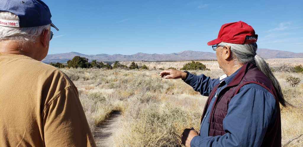 Elmer points towards mountains in background as Allan Kissam from California looks on.